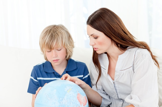 Criança cativada olhando para um globo terrestre com sua mãe