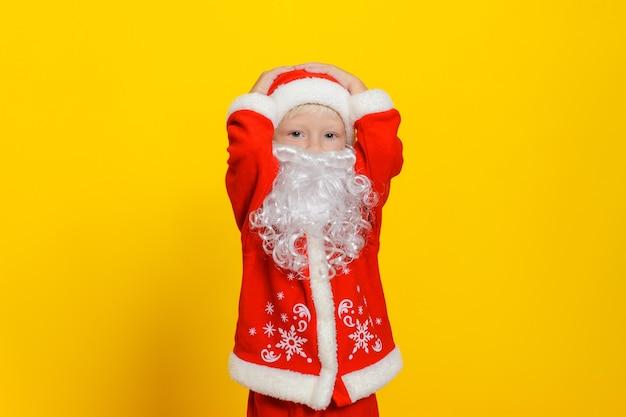 Criança caucasiana com fantasia de papai noel de ano novo e barba branca artificial segurando sua cabeça