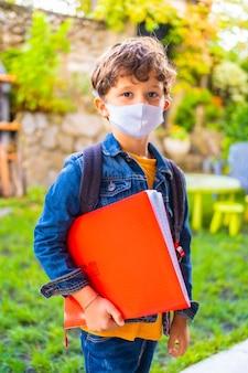 Criança caucasiana com máscara facial pronta para voltar às aulas. nova normalidade, distância social, pandemia de coronavírus, covid-19. jaqueta, mochila e um bloco vermelho para anotações na mão
