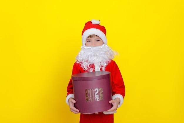 Criança caucasiana de seis anos de idade segura uma grande caixa de presente redonda com as palavras ano novo de 2022 nas mãos
