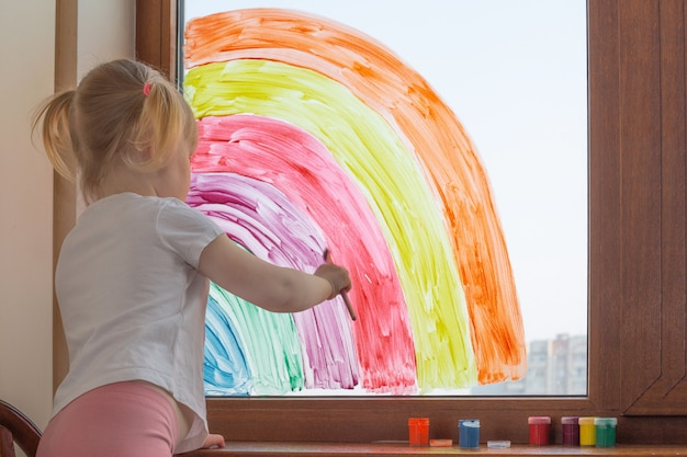 Criança caucasiana menina desenha um arco-íris na janela