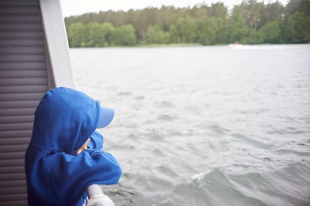 Criança caucasiana, observando a água do convés durante a viagem de navio