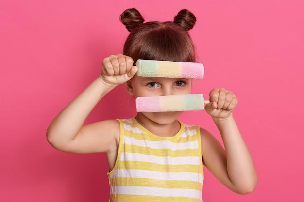 Criança caucasiana se escondendo atrás de dois sorvetes de frutas, vestindo roupas de verão, pequena menina de cabelos escuros em forma lúdica de criança despreocupada.