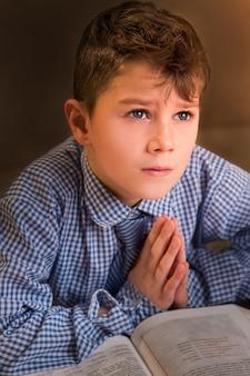 Criança chateada na camisa orando. criança triste reza ao lado do livro. ele encontrará paz. tempos difíceis para o jovem.