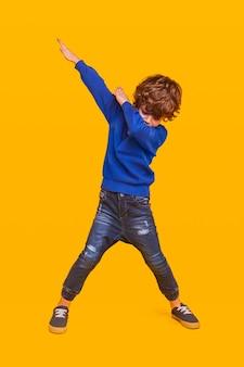Criança cheia de energia dançando em amarelo