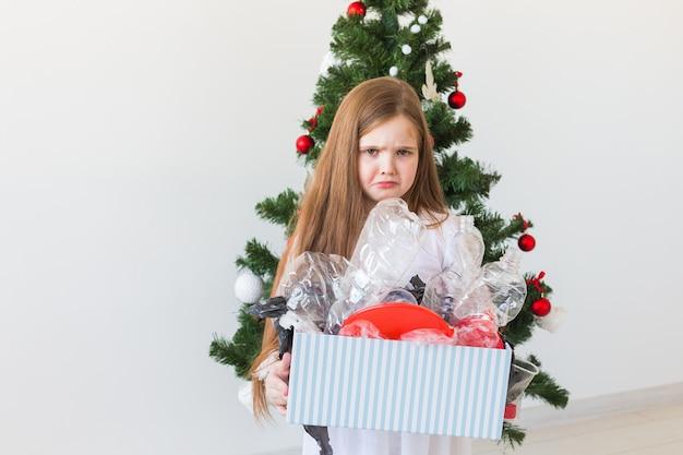 Criança chocada parece com olhos abertos e expressão preocupada segurando uma caixa com o lixo