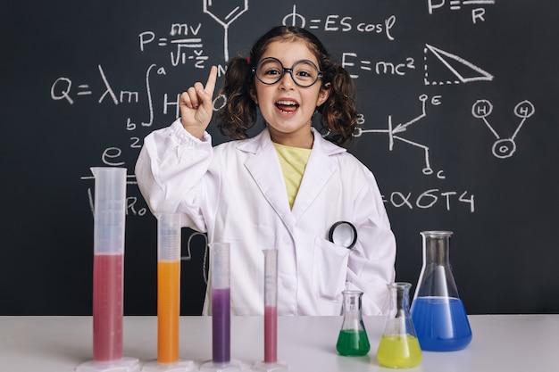 Criança cientista de óculos tendo uma ideia