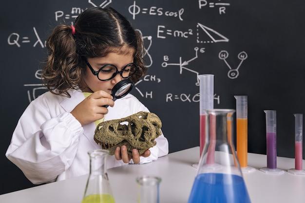 Criança cientista estudando um crânio de dinossauro