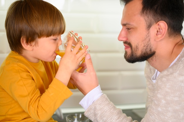 Criança close-up, bebendo suco laranja