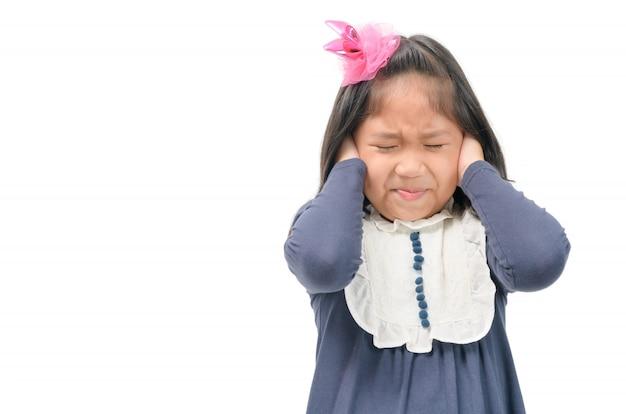 Criança cobrindo as orelhas com as mãos do barulho.