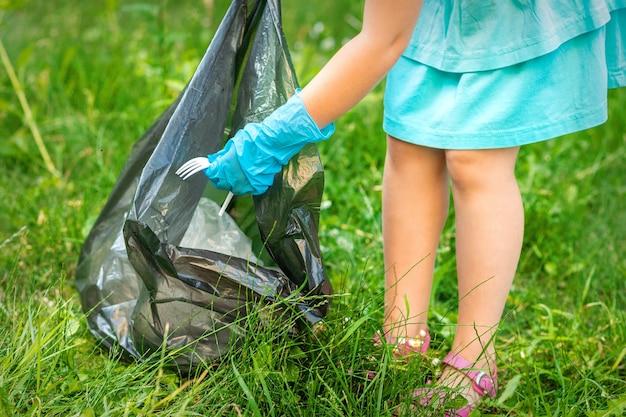 Criança coleta lixo plástico da grama jogando lixo em um saco de lixo no parque