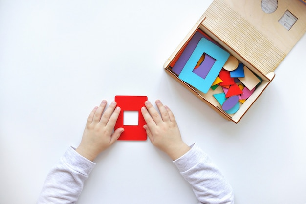 Criança coleta um classificador brinquedos de lógica educacional para crianças