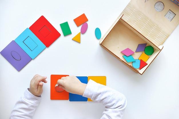 Criança coloca o círculo laranja em jogo. aprendendo cores e formas. a criança recolhe um classificador brinquedos de lógica educacional para crianças