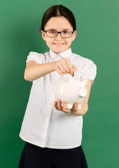 Criança colocando moedas no cofrinho