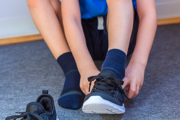 Criança colocar um par de tênis. pernas do jovem rapaz em tênis de moda têxtil preto. roupa casual na moda infantil e moda de rua. fechar-se