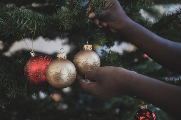 Criança colorida pendurar bugiganga de natal na árvore de férias
