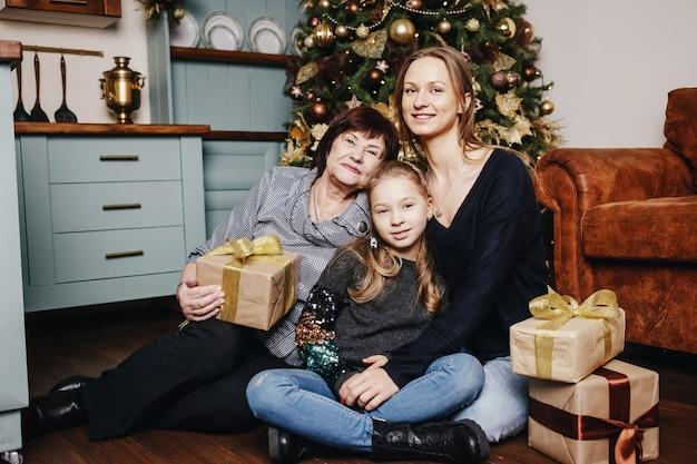 Criança com a mãe e a avó estão sentadas abraçando contra uma árvore de natal.