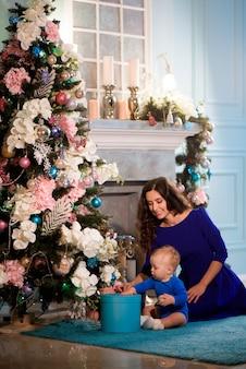 Criança com a mãe na sala festivamente decorada com árvore de natal