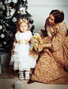 Criança com a mãe perto de árvore de natal.