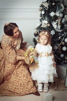 Criança com a mãe, recebendo perto de árvore de natal.