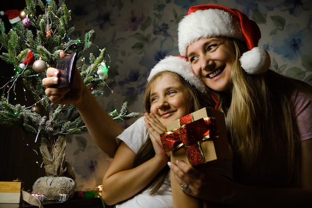 Criança com a mãe usando chapéus de papai noel em uma videochamada no dia de natal, sentada em um sofá na sala de estar com a árvore de natal em casa