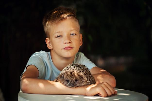 Criança com animal de estimação. menino e ouriço, olhando para a câmera.