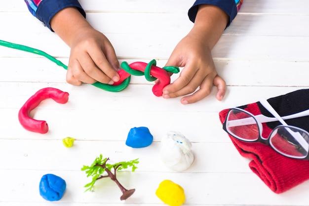 Criança com argila e usando a criatividade para fazer linha vermelha