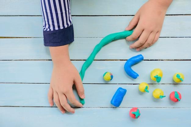 Criança com argila e usando criatividade para fazer linha e frutas