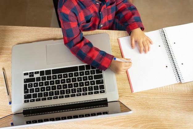 Criança com as mãos escrevendo em um caderno e um laptop sobre uma mesa