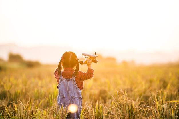 Criança com avião de brinquedo na natureza ao pôr do sol