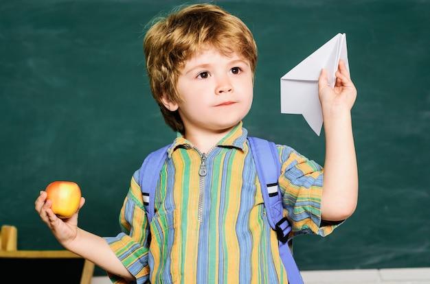 Criança com avião de origami na escola primária. menino brincar com o avião de papel. voltar para a escola e momentos felizes.