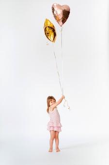 Criança com balões em forma de coração e estrelas