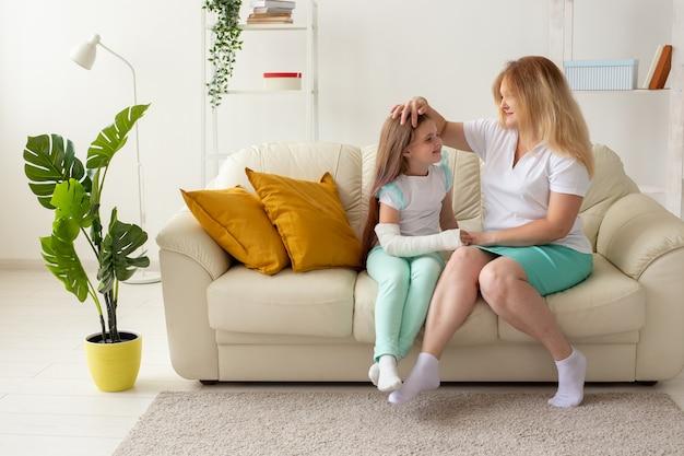 Criança com braço quebrado e gesso passa um tempo em casa com a mãe. doenças da infância, um positivo