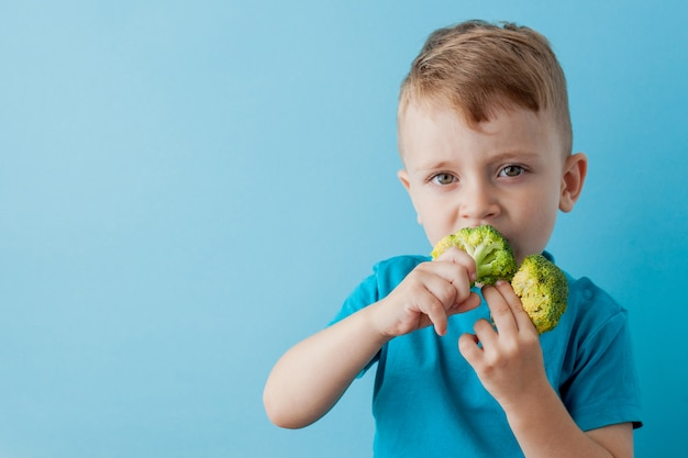 Criança com brócolis nas mãos, sobre fundo azul. vegan e conceito saudável