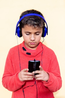 Criança com cabelo escuro, ouvindo música com hadphones azuis e um celular