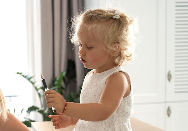 Criança com caneta em casa durante quarentena Foto gratuita