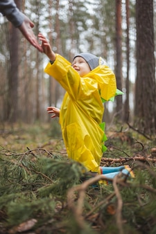 Criança com capa de chuva amarela caminhando na floresta depois da chuva, sentada no chão entre galhos de pinheiro, mãe estende a mão e o ajuda a se levantar