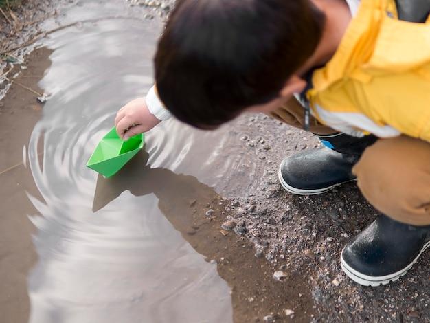 Criança com capa de chuva brincando com um barco de plástico