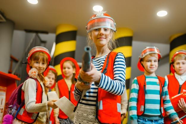 Criança com capacete e uniforme com mangueira nas mãos, brincando de bombeiro