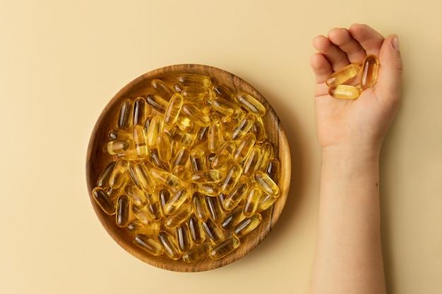Criança com cápsulas amarelas na mão. prato com vitaminas perto dele.