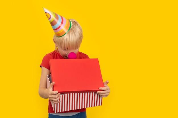 Criança com chapéu de festa olhando para uma caixa de presente com curiosidade
