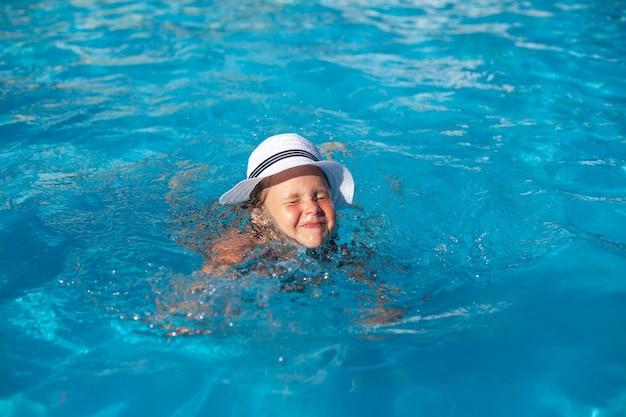 Criança com chapéu de palha branco está brincando na água, garota encantadora feliz toma aulas de natação e aperta os olhos ...
