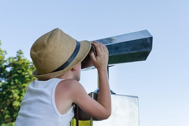 Criança com chapéu de palha, olhando pelo telescópio para turistas no céu azul