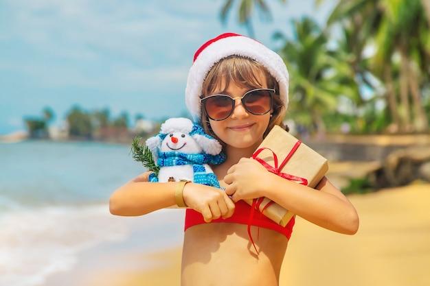 Criança com chapéu de papai noel e óculos de sol segurando presentes na praia