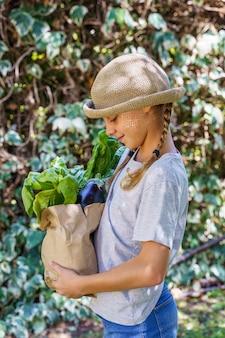 Criança com chapéu de vime no horário de verão com compras do mercado ecológico