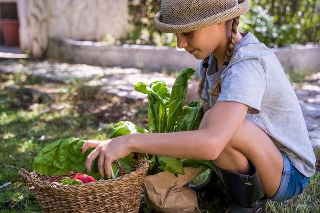 Criança com chapéu de vime no horário de verão com compras na cesta de vime