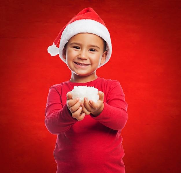 Criança com chapéu e neve de santa em suas mãos