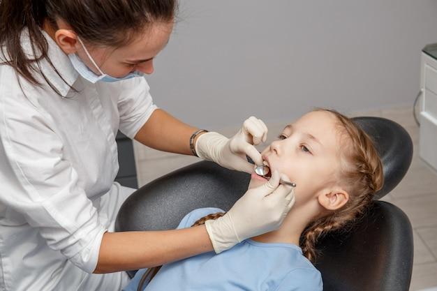 Criança com check-up odontológico por especialista em consultório dentário
