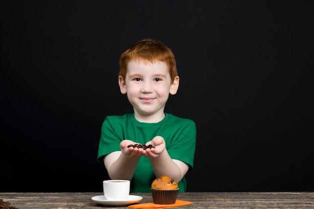 Criança com comida comendo um bolinho e brincando com café