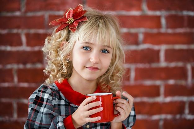 Criança com copo vermelho de cacau quente ou chocolate com marshmallow.